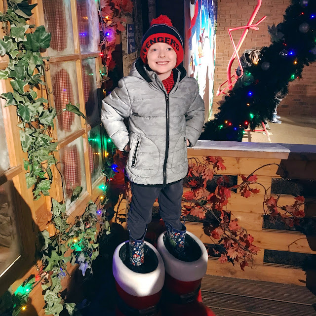 Little boy standing in a large pair of santas boots in front of a festive looking house