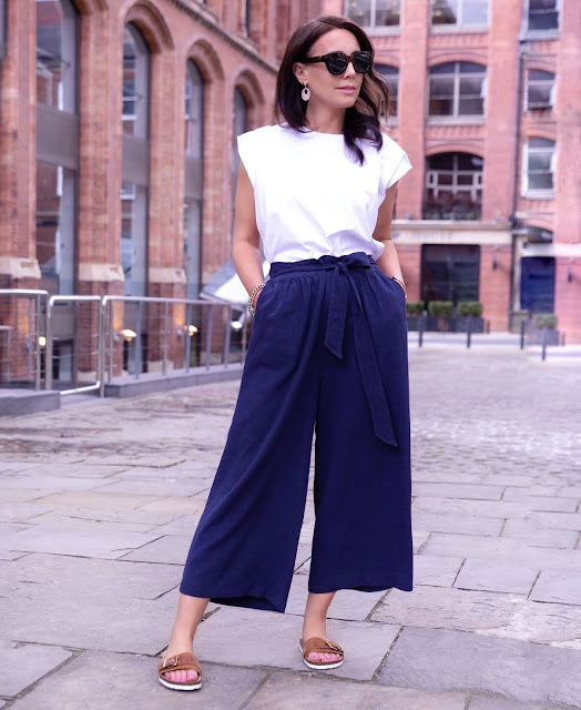 woman in navy culottes and white top