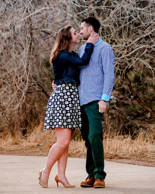 a woman gently caresses her fiances neck during a photo session for their engagement pictures in Boulder Colorado