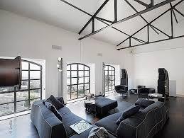 ruang tamu dinding berwarna putih dengan sofa warna hitam lantai dari kayu berwarna coklat meja kaca