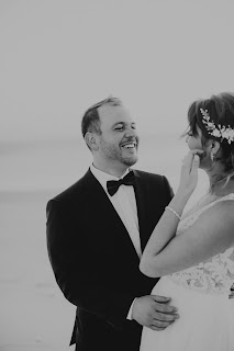 Groom candidly laughing at wife.