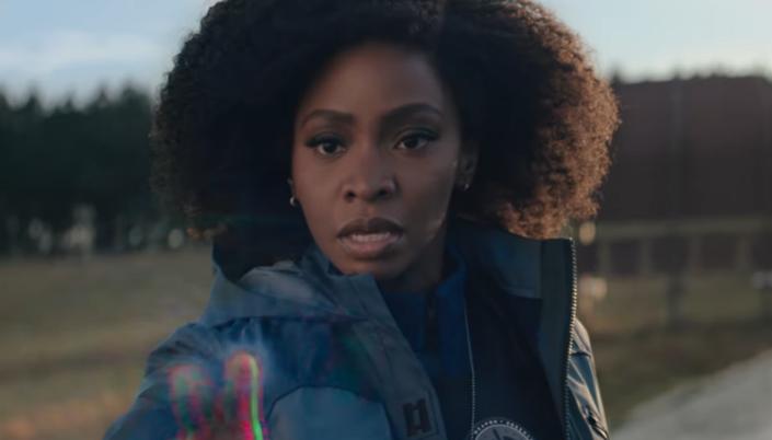Imagem: a personagem Monica Rambeau, uma mulher negra com o cabelo crespo longo, usando um casaco azul, tocando o campo de força transparente que se parece com o chiado de tela de televisão, no fundo árvores de um campo ao lado de estrada.