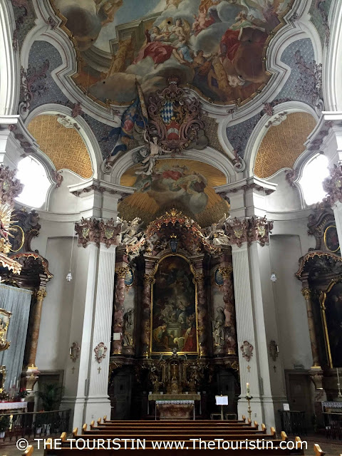 Altar and ornate pillars under a painted ceiling in a Rococo church.