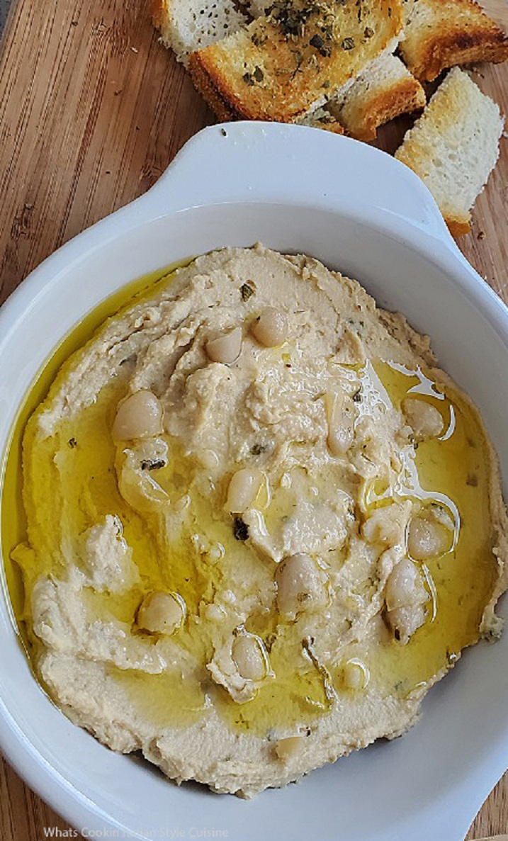 this is white bean dip with olive oil on top in a white baking dish