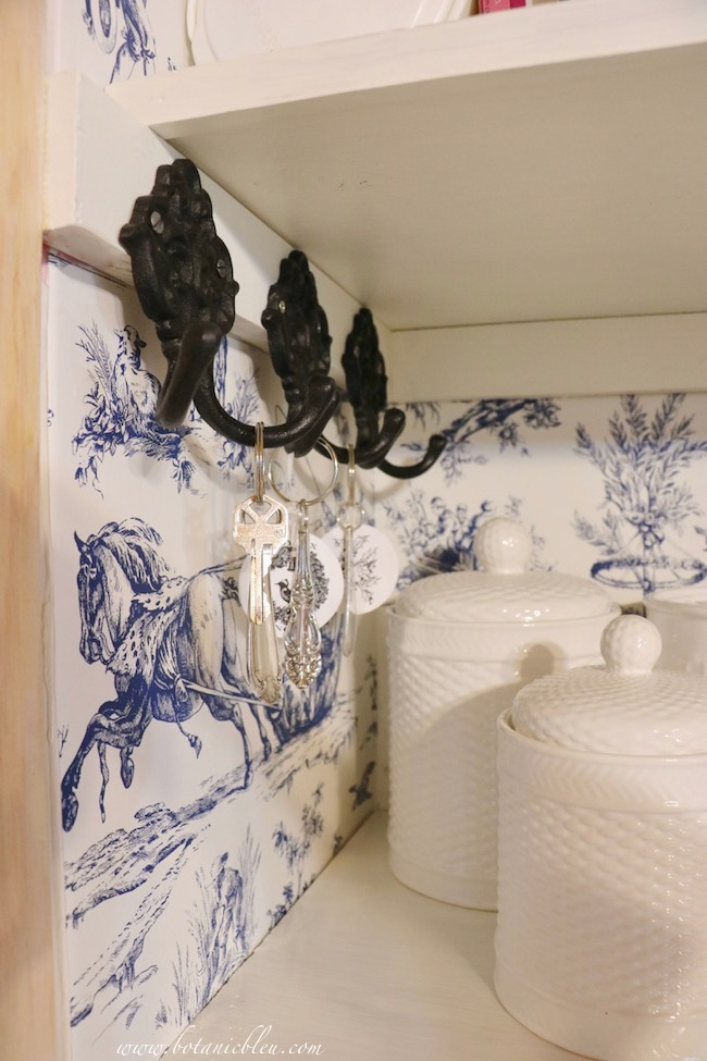 Toile pantry updated with black iron double hooks holding vintage silver plate key rings