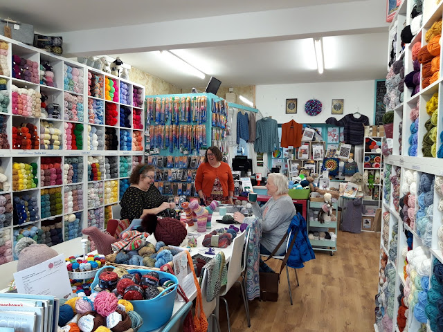 A photo of the interior of a yarn shop.  In the centre is a long table covered with baskets of yarn, pattern books and knitted sock and hat samples.  There are three ladies in the centre of the picture - one seated at the table on the left wearing a black spotty top, one standing behind the table wearing a rust-coloured cardigan and one seated at the table on the right wearing a grey cardigan.  She is holding a mug of tea and all three are laughing.  Behind them on every wall are balls of yarn, knitting needles, knitted garments and pattern books and kits.