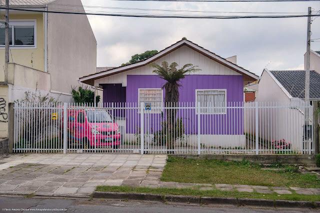 Carro rosa em frente a casa roxa e branca