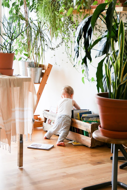 A toddler emptying a child's book case in the family home