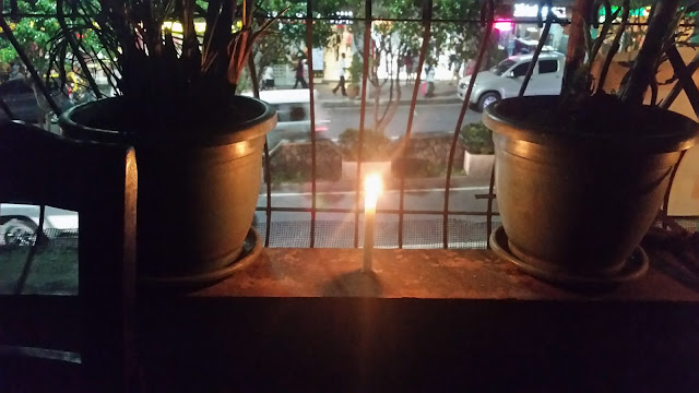Lighted Candle at night with two plastic pots at the porch