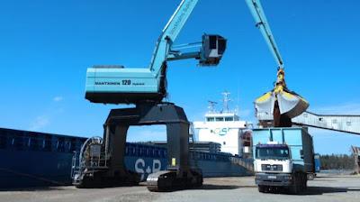 Lastkran tömmer skopan i en lastbil, bredvid ligger ett lastfartyg vid kaj.