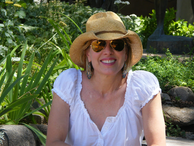 Picture of Linda Vater in straw hat sitting in garden.