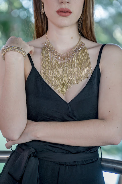 Girl wearing a black dress and a plastron necklace.