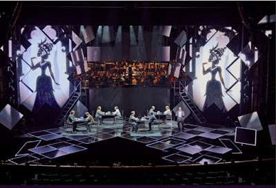 photo of stage showing papercut puppets as backdrop, and 4 pairs of people playing chess, on stage. Orchestra visible  above the stage