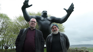 Robert Lloyd and Stewart Lee in front of a giant gorilla statue