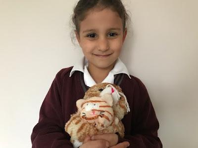 Child holding cuddly toys