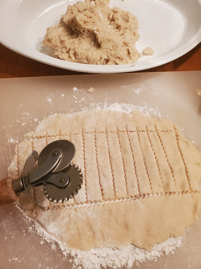this is a lattice crust being cut out to a this is a ricotta Italian cheesecake called cassata made at Easter