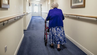 An elderly woman walking with a rollator walker down a hall