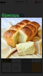 На столе лежит буханка белого хлеба бриошь, отрезан ломтик