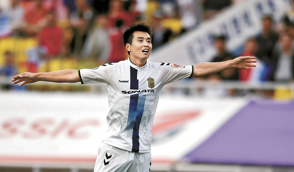 Having scored his team's third goal, Lee Dong-gook celebrates Jeonbuk Hyundai Motors win over Suwon Samsung Bluewings