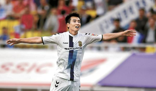 Having scored his team's third goal, Lee Dong-gook celebrates Jeonbuk Hyundai Motors win over Suwon Samsung Bluewings