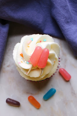looking down at summery cupcake with fluffy white frosting and pink candy popsicle topper