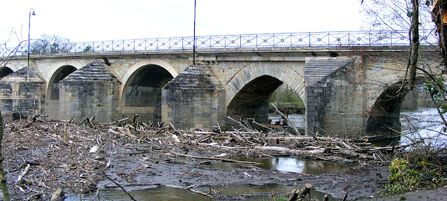 Log jam of debris by the bridge at Descartes.  Indre et Loire, France. Photographed by Susan Walter. Tour the Loire Valley with a classic car and a private guide.