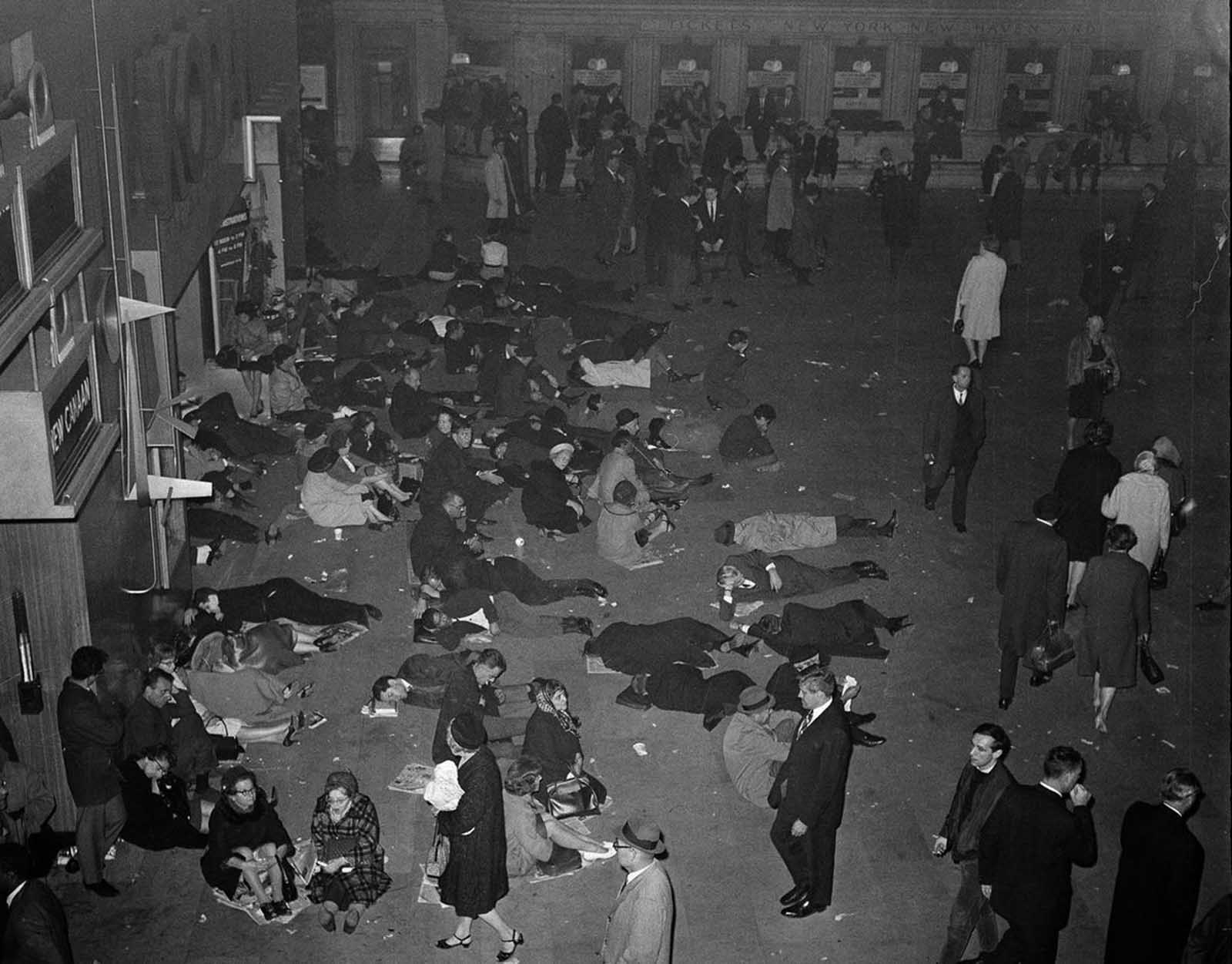 People sleep sitting and lying down at Grand Central Terminal's main waiting room in New York, during a massive power failure, on November 9, 1965. The area is lit with emergency lighting. The blackout affected New York State, most of New England, parts of New Jersey, Pennsylvania, and Ontario, Canada.