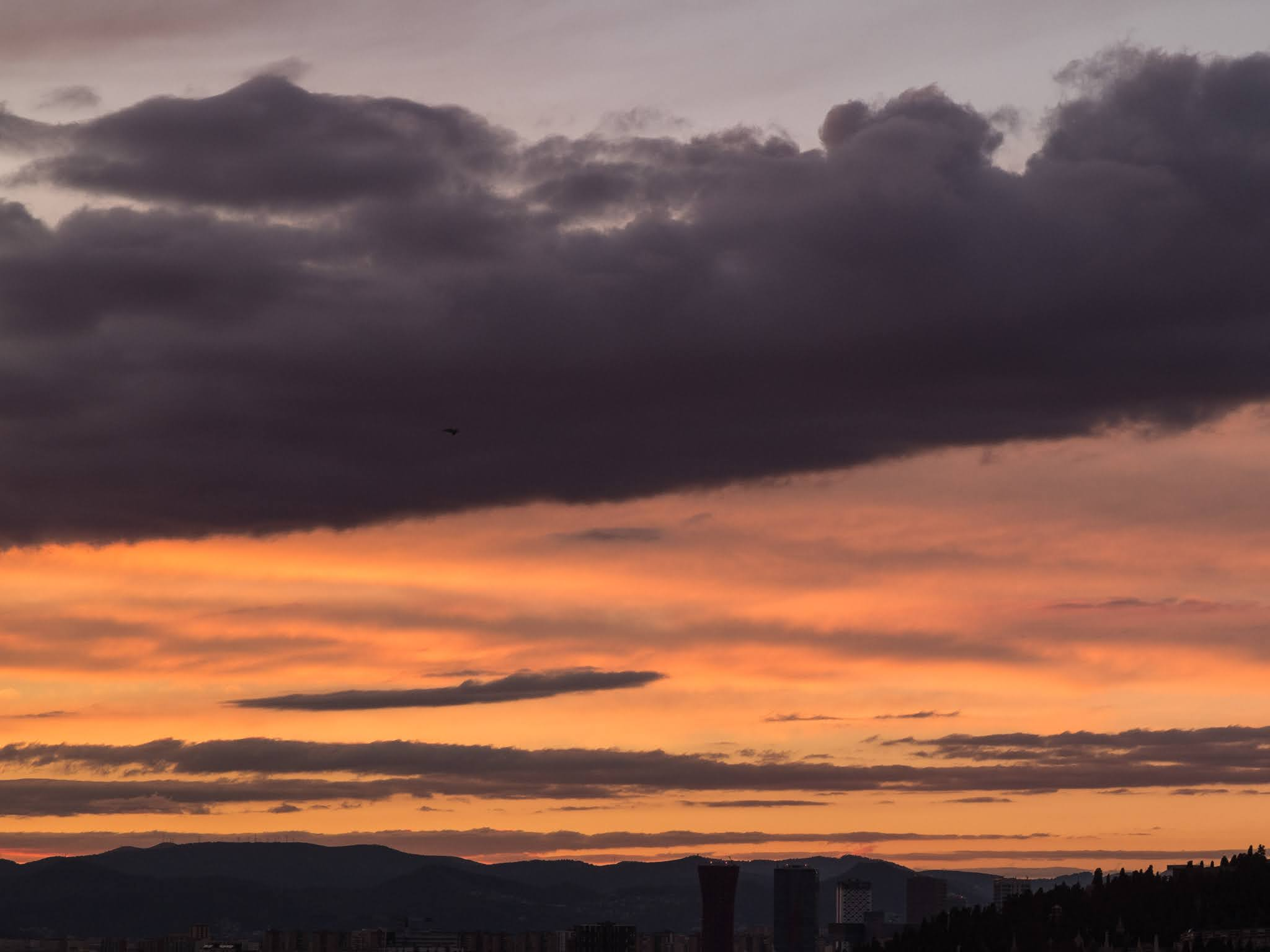 Dramatic sunset clouds over a mountain range as seen from the port of Barcelona.
