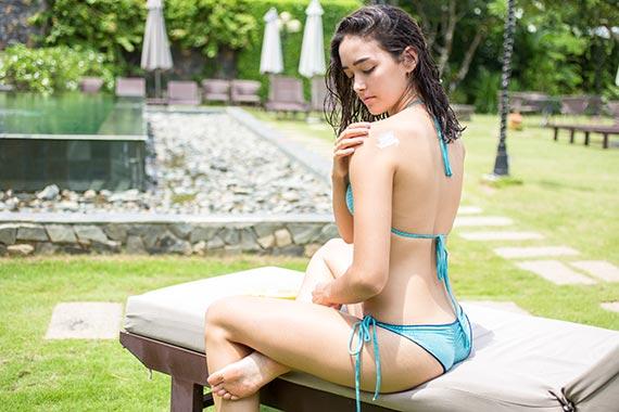 beautiful-young-woman-applying-sunscreen-lotion