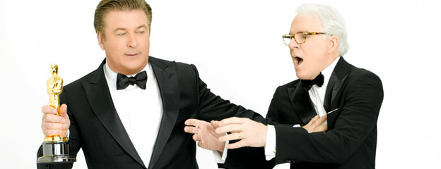 Alec Baldwin holding Steve Martin at arm's length as Martin reaches longingly for Oscar statuette in Baldwin's other hand