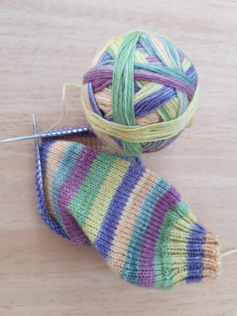 Image shows a stripey knitted sock with a ball of sock yarn