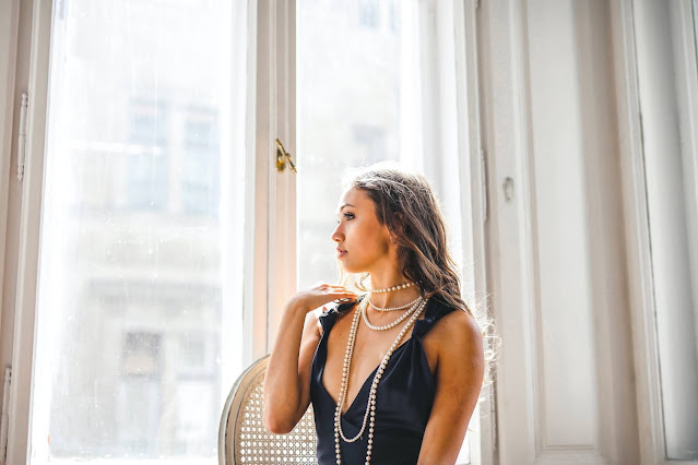 A woman wearing a black dress and necklace looking out her window.