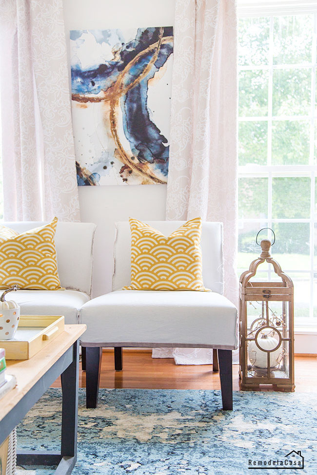mustard pillowcases and wooden lantern with pumpkin decor