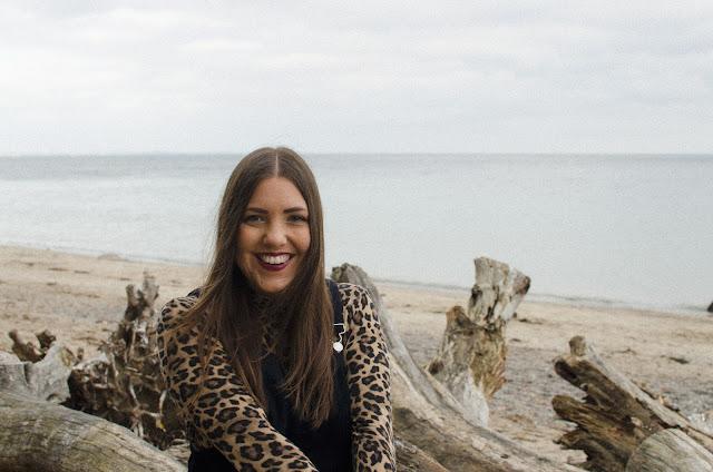Lea sitzt am Strand auf einem Baumstamm und lacht herzlich