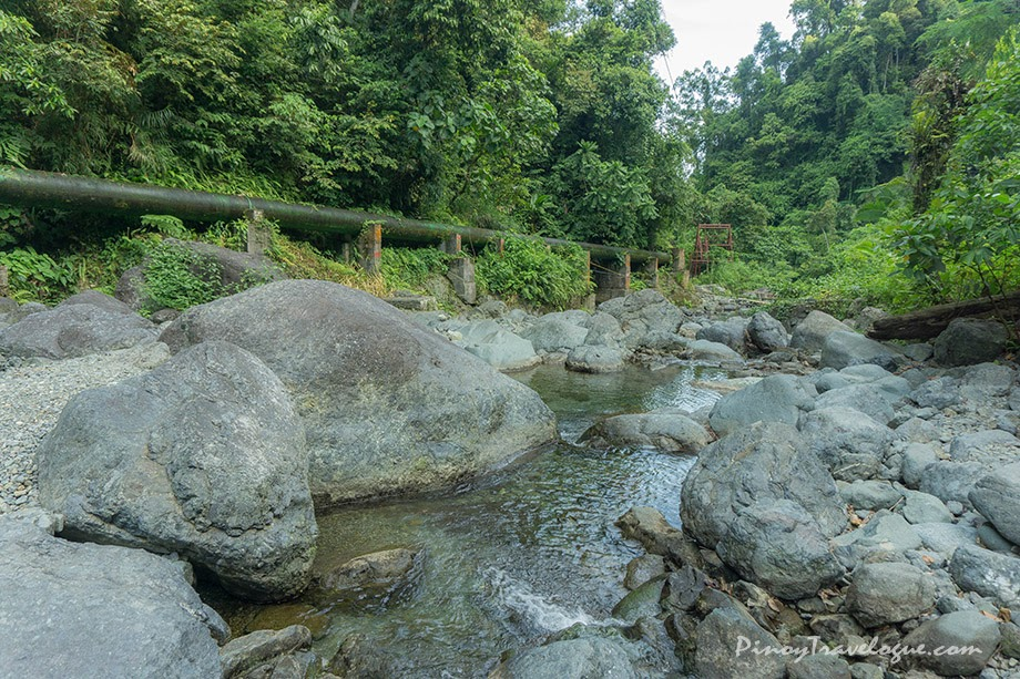 Boulders, large metal pipes and streams amid the lush jungle
