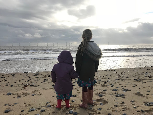 Sisters on holiday looking out to sea on a cold beach