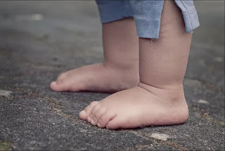 A small child's bare feet standing on pavement in Azilda, ON