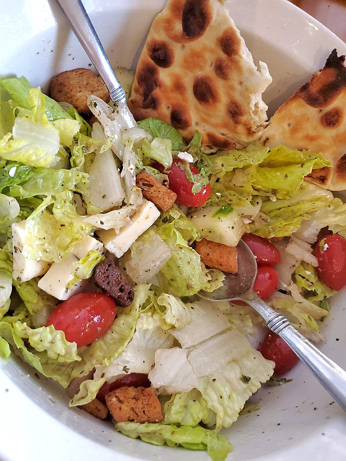 homemade salad greek dressing on top of a tossed salad