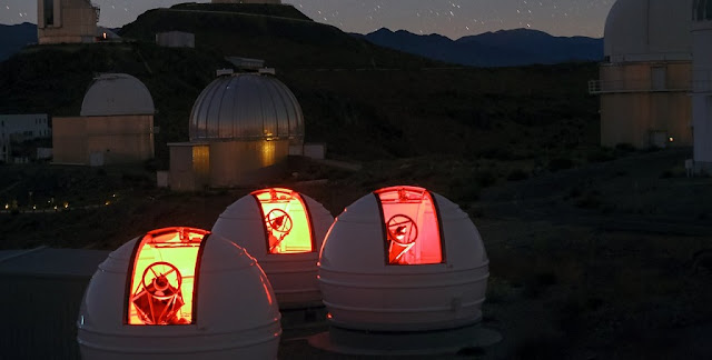 The ExTrA telescopes are sited at ESO's La Silla Observatory in Chile. They will be used to search for and study Earth-sized planets orbiting nearby red dwarf stars. ExTrA's novel design allows for much improved sensitivity compared to previous searches.  This nighttime view shows the three ExTra domes in the foreground and many of the other telescopes at ESO's La Silla Observatory behind.  Credit: ESO/Emmanuela Rimbaud
