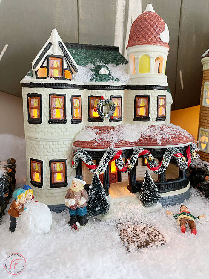 A nostalgic Victorian Christmas Village display on a fireplace mantle. A two level miniature Christmas scene with sentimental value.