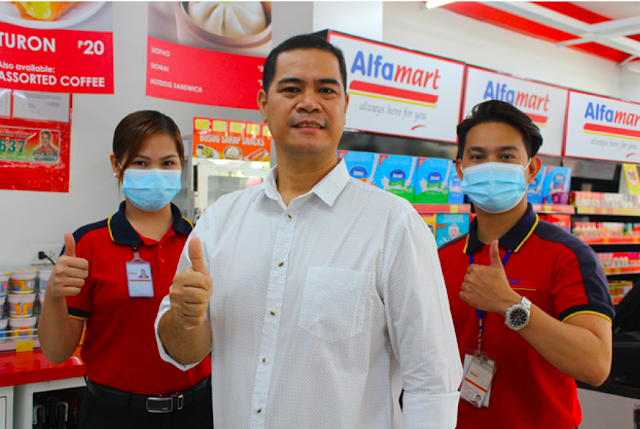 """Martiniano """"Degs"""" Valencia (center), a former OFW, is enjoying the fruits of his decision to become a partner and co-owner of the Alfamart in his hometown in Sta. Rita, Pampanga. Degs' branch helped his local community survive the pandemic during the resulting lockdowns."""