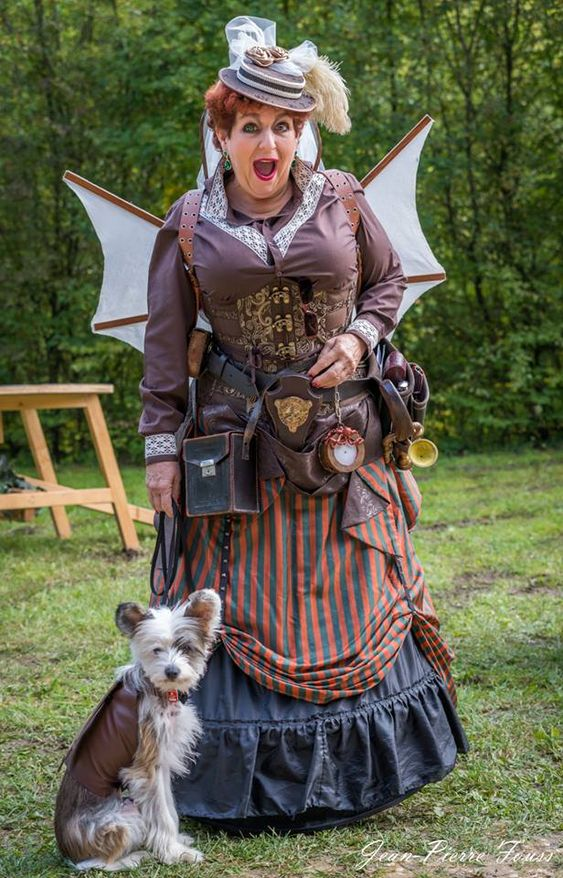 Steampunk woman wearing wings, hat, corset, skirt and blouse. Walking her steampunk dog who has wings (steampunk pet costumes)