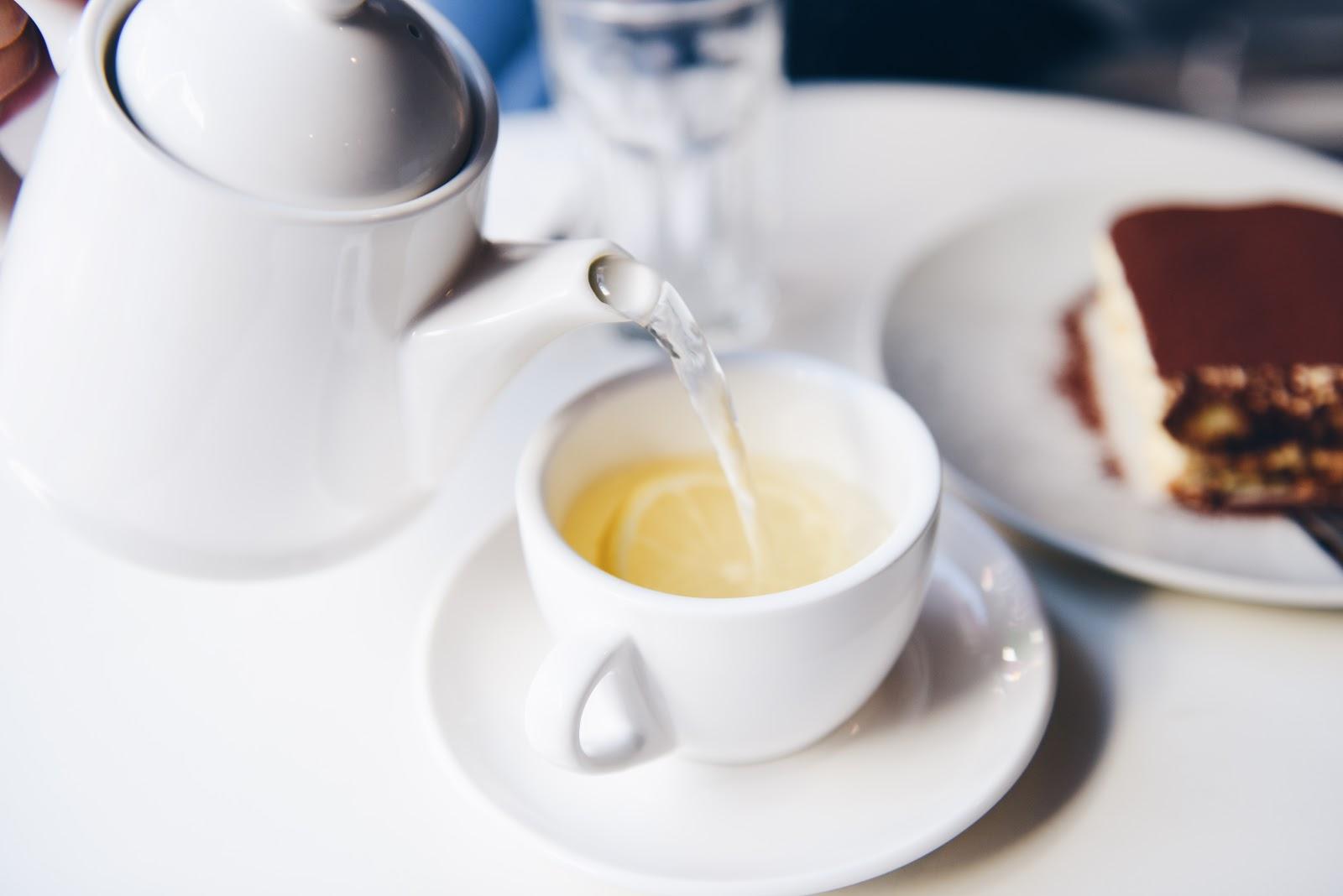 真っ白なティーカップにポットからレモンティーの湯が注がれている