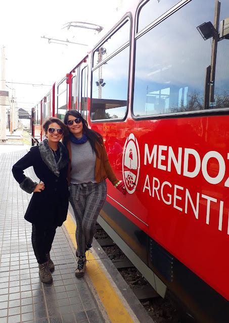 duas amigas abraçadas do lado de um trem