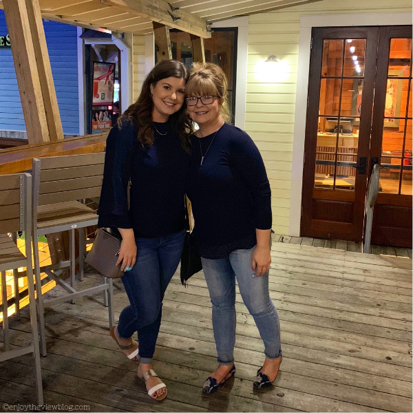 mother and daughter standing in front of a restaurant