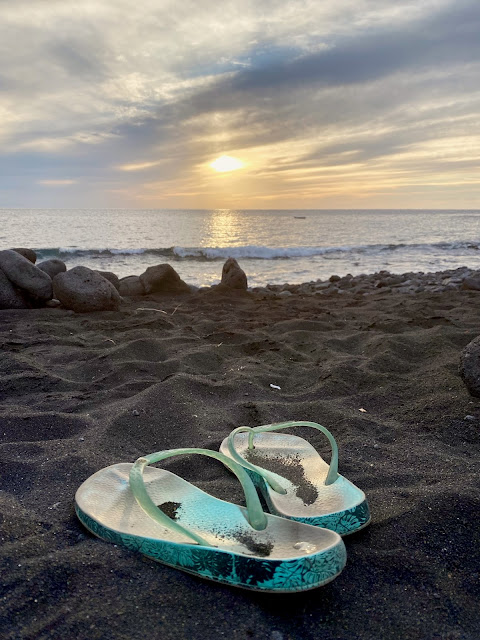 Flip flops on the black volcanic sand, sunset at the beach, near Tasartico, Gran Canaria, Spain