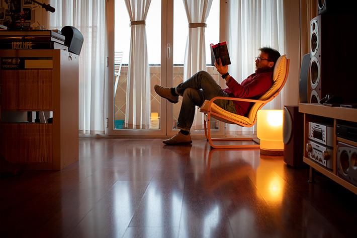 Sentado y leyendo un libro junto a las ventanas.