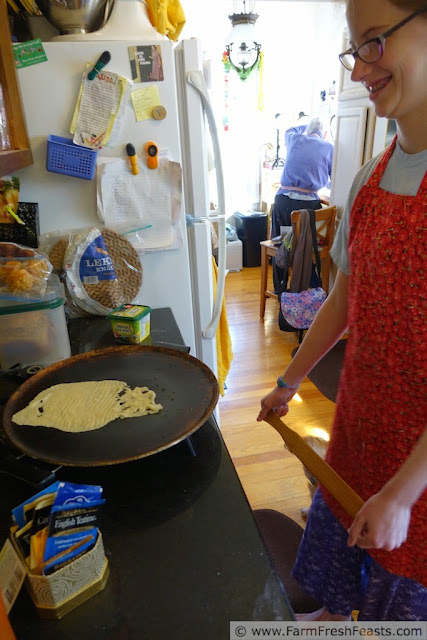 photo of a misshapen piece of lefse cooking on the griddle