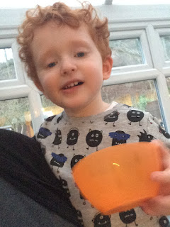 Red haired toddler holding a small orange plastic bowl