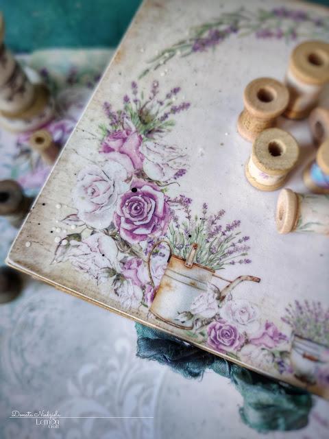 Przepiękna kompozycja w stylu prowansalskim: lawendowy wianek, w który wplecione są fioletowe i białe róże oraz rustykalna konewka i dzbanuszek